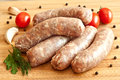 Uncooked sausages with vegetables on the chopping board Stock Images