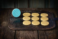 Uncooked shortbread with stamp before being to be baked blue inscription home made over black cutting board dark rustic style Stock Photo