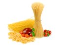 Uncooked spaghetti with tomato and arugula on a white background Royalty Free Stock Photos