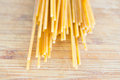 Uncooked spaghetti on wooden background Royalty Free Stock Photos