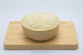 Uncooked white rice in bowl on wooden board Royalty Free Stock Photo