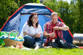 Uncork the prosecco happy young couple is relaxing on a camping Royalty Free Stock Photo