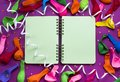 Uncovered notebook for records on a purple festive background colored balloons streamers Top view festive background copy space Royalty Free Stock Photo