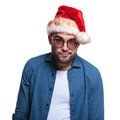 Undecided young man in santa hat is looking at the camera on white background Stock Images
