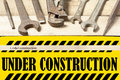 Under construction board with repair tools. Wrench on wooden background Royalty Free Stock Photo