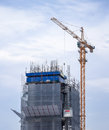 Under construction high building showing its structure with tall crane isolated on cloudy sky Royalty Free Stock Image