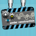 Under construction plate with gears and the text written with white letters Stock Photography