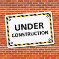 Under construction sign on brick wall Royalty Free Stock Image