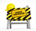 Under construction sign and hardhat on barrier Stock Photos