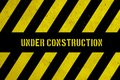 Under construction warning danger sign with yellow and black stripes painted over concrete wall coarse facade texture background.