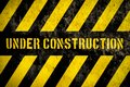 Under construction warning sign with yellow and dark stripes painted over concrete wall coarse facade as texture background Royalty Free Stock Photo