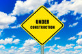 Under construction yellow road sign with clouds and sky in background Royalty Free Stock Image
