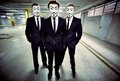 Under cover portrait of anonymous masked businessmen standing in an empty underground parking lot Royalty Free Stock Photo