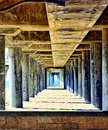 Under the pier looking a and through tunnel made by a s pylons to ocean Stock Images