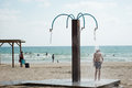 Under the spray near the sea boy on insipid shower Royalty Free Stock Images