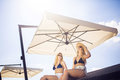 Under the sunshade a photo of two female friends sitting big and relaxing Stock Photography