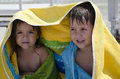 Under the towel two kids just out of sea seeing shelter a beach Royalty Free Stock Photos
