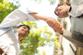 Under view perspective of two young attractive businessmen shaking hands against a blue sky with trees in the city Royalty Free Stock Images