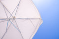 Under a white beach umbrella looking up into the opened parasol with its metal spokes against blue sunny sky Royalty Free Stock Photography