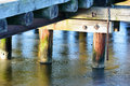 Underside of pier the an old wooden or jetty in winter ice cover the water fine colors on the wood and reflections in the ice iron Royalty Free Stock Photos