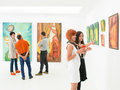 Understanding art at exhibition opening people in an gallery talking about the colorful paintings displayed on walls Royalty Free Stock Photography