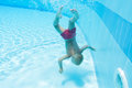 Underwater boy dived to the bottom of pool Stock Photography