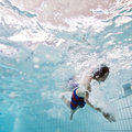 Underwater breast crawl man swimming a in an indoors swimming pool seen from below the water surface Stock Photos