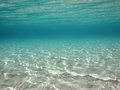 Underwater ripples of sunlight in clear shallow water reflected on a sandy sea floor Stock Photos