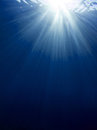 Underwater sun rays against the deep blue Royalty Free Stock Photo