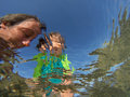 Underwater view of a father and her daughter with distorted face