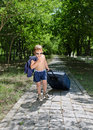 Undressed child young with sunglasses and baggage walking on the road Stock Image