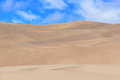 Undulating sand dunes and blue sky waves in in the desert Stock Photos