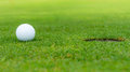 Une boule de golf au trou Photo libre de droits