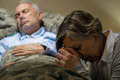 Uneasy senior woman praying for sick man women men sleeping in hospital bed Stock Image