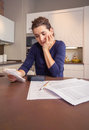 Unemployed and divorced woman with debts reviewing many her monthly bills Royalty Free Stock Image