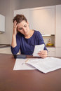 Unemployed and divorced woman with debts reviewing many her monthly bills Stock Photography