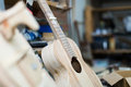 Unfinished acoustic guitar and workshop equipment at background Stock Image