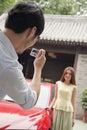 Ung man som tar en bild av hans flickvän och bil Fotografering för Bildbyråer