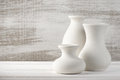 Unglazed ceramic vases three empty white on white wooden table against rustic wooden wall Stock Image