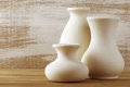 Unglazed ceramic vases three empty white on wooden table against rustic wooden wall toned image shallow dof focus on middle vase Royalty Free Stock Image