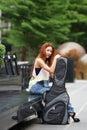 Ungt härligt posera för kvinna som är utomhus med hennes gitarrgigpåse Arkivfoton