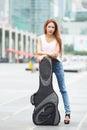 Ungt härligt posera för kvinna som är utomhus med hennes gitarrgigpåse Royaltyfri Bild