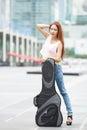 Ungt härligt posera för kvinna som är utomhus med hennes gitarrgigpåse Arkivbild