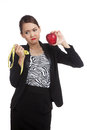 Unhappy Asian business woman diet with red apple and  measuring Royalty Free Stock Photo