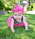 Unhappy baby makes cry face as she crawls on grass with a pink bow on her head Stock Photos