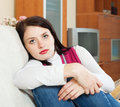 Unhappy brunette woman on sofa at home Stock Image
