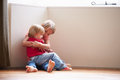 Unhappy children sitting on floor in corner at home young Royalty Free Stock Photos