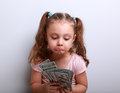 Unhappy confused grimacing kid girl looking on dollars in hands Royalty Free Stock Photo