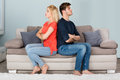 Unhappy Couple With Arms Crossed Sitting On Sofa Royalty Free Stock Photo