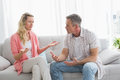 Unhappy couple having an argument on the couch at home in living room Royalty Free Stock Photos